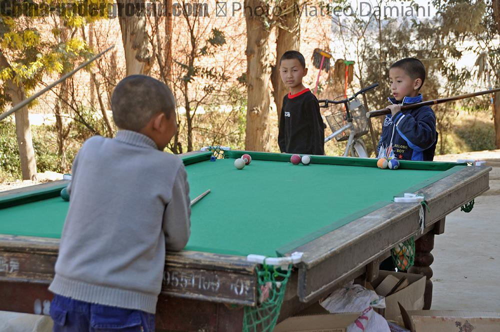 Chinese kid playing snooker