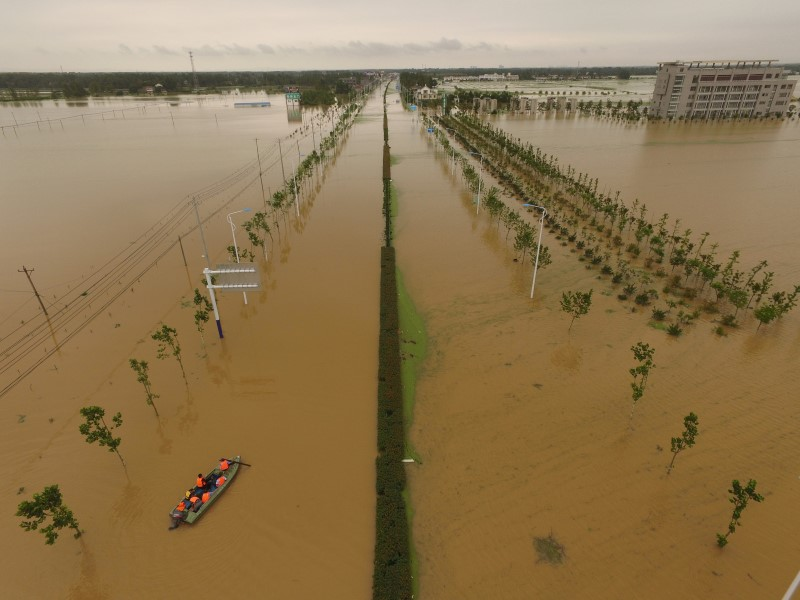 Rescuers take a boat to check around at a flooded road in Shucheng, Anhui Province, China, July 3, 2016. REUTERS/Stringer