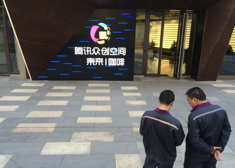 Men stand in front of the gate of Tencent Space, a flagship technology incubator in Tianjin, China, May 17, 2016. REUTERS/Sue-Lin Wong