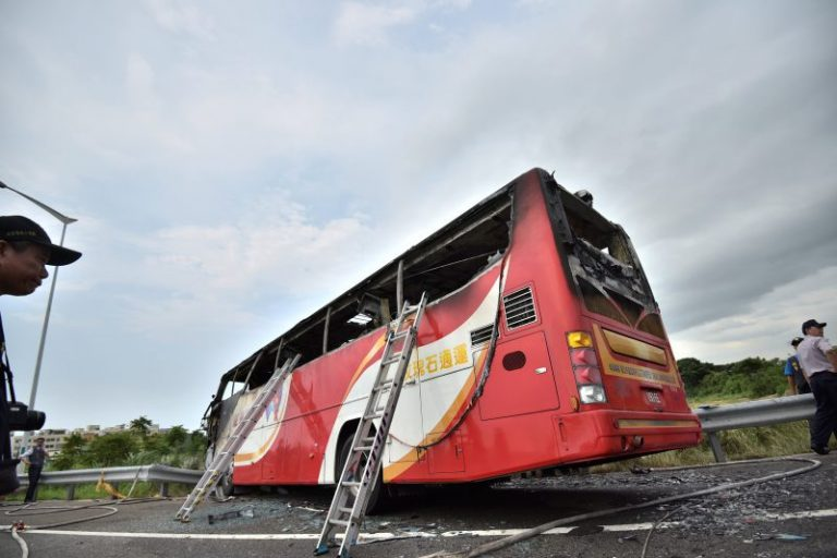 Emergency personnel work around the wreckage of a bus that crashed near Taipei