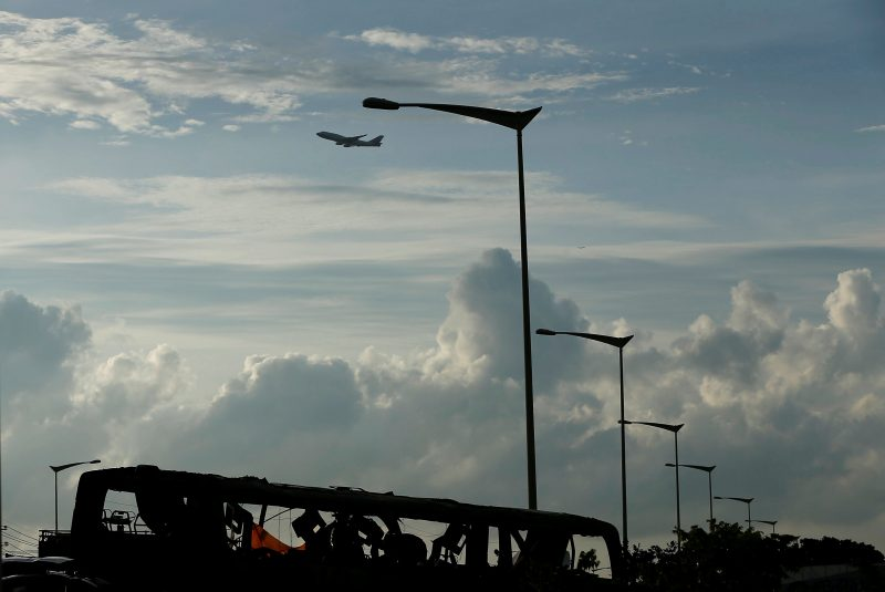 An airplane flies over a bus that crashed en route to Taoyuan airport, just south of the capital Taipei, Taiwan July 19, 2016. REUTERS/Tyrone Siu