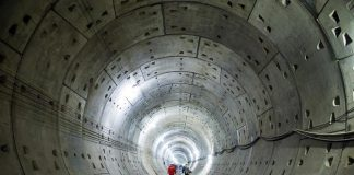 Workers walk along a tunnel of a subway construction site in Changsha, Hunan province