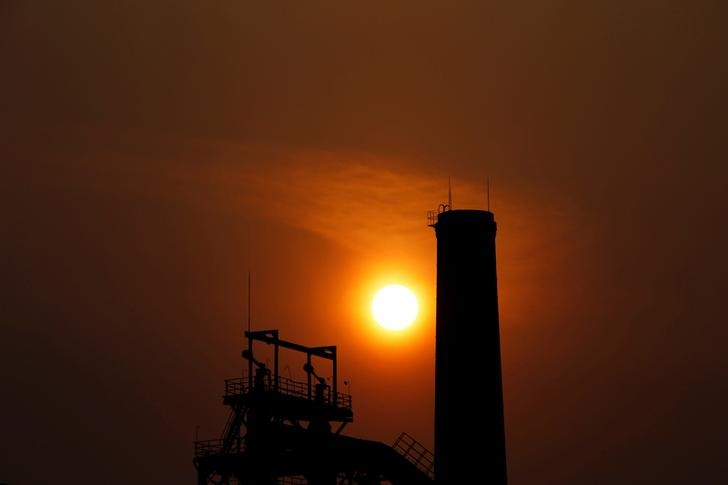 The sun sets behind a chimney of a steel mill in Tangshan, Hebei province