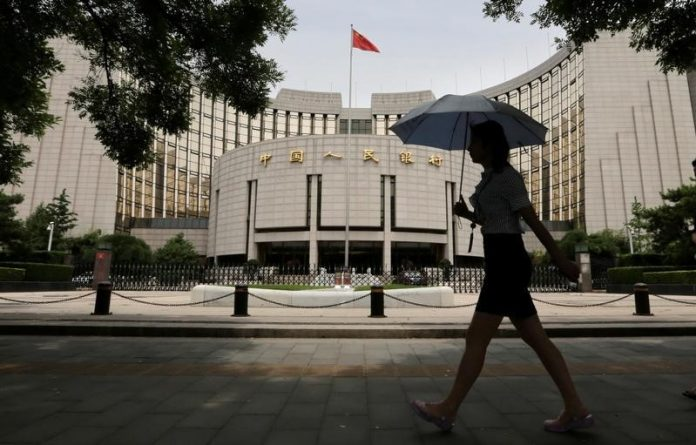 Woman walks past the headquarters of the PBOC in Beijing