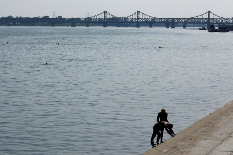 A man receives a massage on the bank of the Yalu river in China's Dandong, Liaoning province, opposite North Korea, September 11, 2016. REUTERS/Thomas Peter