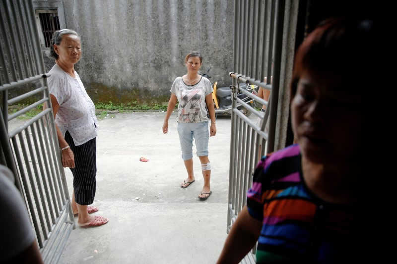 An injured woman and other villagers tell their experience after Tuesday's clashes between security forces and protesters in Wukan, Guangdong province, China, September 14, 2016. REUTERS/Damir Sagolj