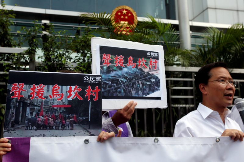 """Protesters demonstrate with placards which read """"Support Wukan village"""" outside China Liaison Office in Hong Kong, China September 14, 2016.      REUTERS/Bobby Yip"""