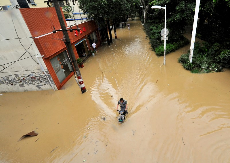 A man rides through a flooded street after Typhoon Meranti made landfall on southeastern China, in Fuzhou, Fujian province, China, September 15, 2016. REUTERS/Stringer