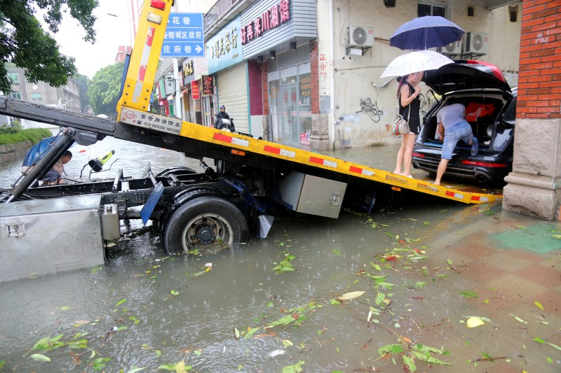 People prepare to move a car onto a trailer after Typhoon Meranti made landfall on southeastern China, in Quanzhou, Fujian province, China, September 15, 2016. REUTERS/Stringer