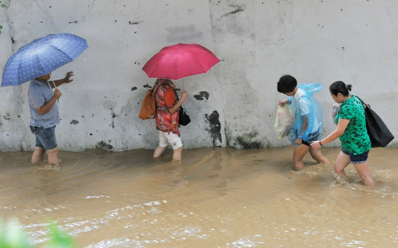 People wade through a flooded street after Typhoon Meranti made landfall on southeastern China, in Fuzhou, Fujian province, China, September 15, 2016. REUTERS/Stringer