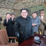 North Korean leader Kim smiles as he guides a test fire of a new multiple launch rocket system in this undated photo released by North Korea's KCNA in Pyongyang