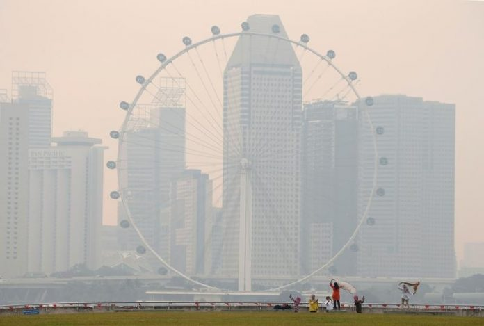 People take photos near the Singapore Flyer observatory wheel shrouded by haze