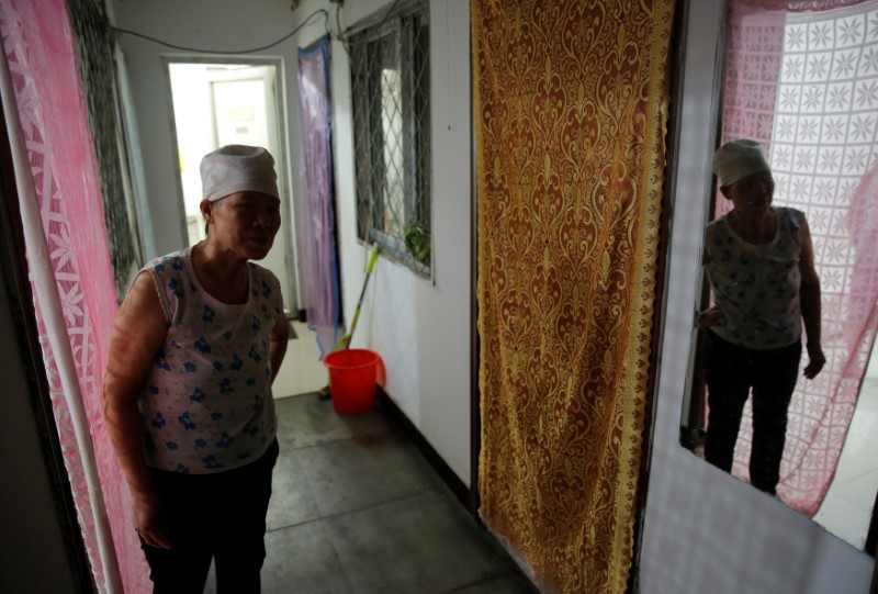 Huang is reflected in a mirror as she stands in front of her room at the accommodation where some patients and their family members stay while seeking medical treatments in Beijing, China, June 22, 2016. REUTERS/Kim Kyung-Hoon