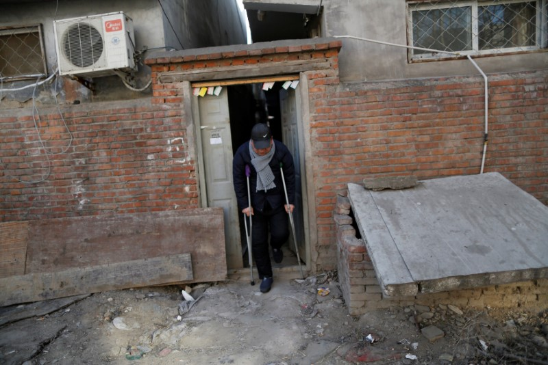 Yuan Yunping, who has melanoma of the foot, leaves the accommodation where some patients and their family members stay while seeking medical treatment in Beijing, China, January 13, 2016. REUTERS/Kim Kyung-Hoon
