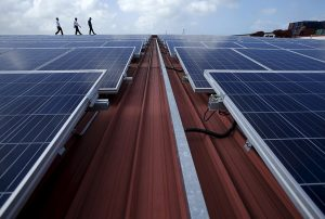 Sun Electric's Chief Executive Officer Matthew Peloso (R) walks along rows of rooftop solar panels, operated under the company's SolarSpace energy retail programme at a factory in Singapore February 29, 2016.\n\nREUTERS/Edgar Su