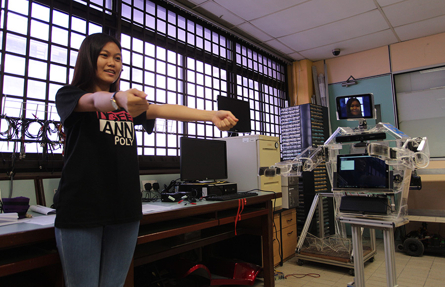 Teng Jin Li, a student in the Electrical Engineering Division, Ngee Ann Polytechnic, demonstrates a telepresence application by getting a robot named RoboCoach Xuan 1 to give a virtual hug in the Electrical Product Development Lab in Singapore July 1, 2016. RoboCoach Xuan 1 is being used as a platform to develop and test a telepresence application, which will be used to address the issue of social isolation among elderly people. \n\nMinistry of Communications & Information via Reuters