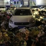 Illegally parked SUV blocks path to waste center, garbage collectors surround the SUV with tons of garbage