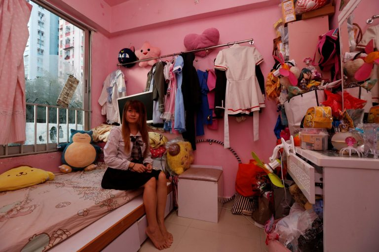 Manman Luk poses inside her sub-divided unit in Hong Kong