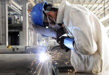 Employee welds the exterior of a vehicle along a production line at a factory in Qingdao