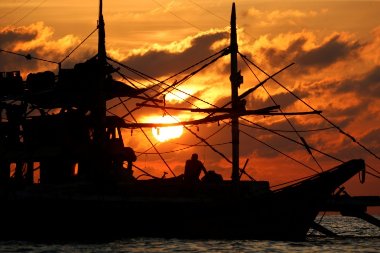 A Philippine fisherman sits on his boat during sunset at the disputed Scarborough Shoal