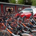 Mobike's shared bikes are parked around a car in Beijing