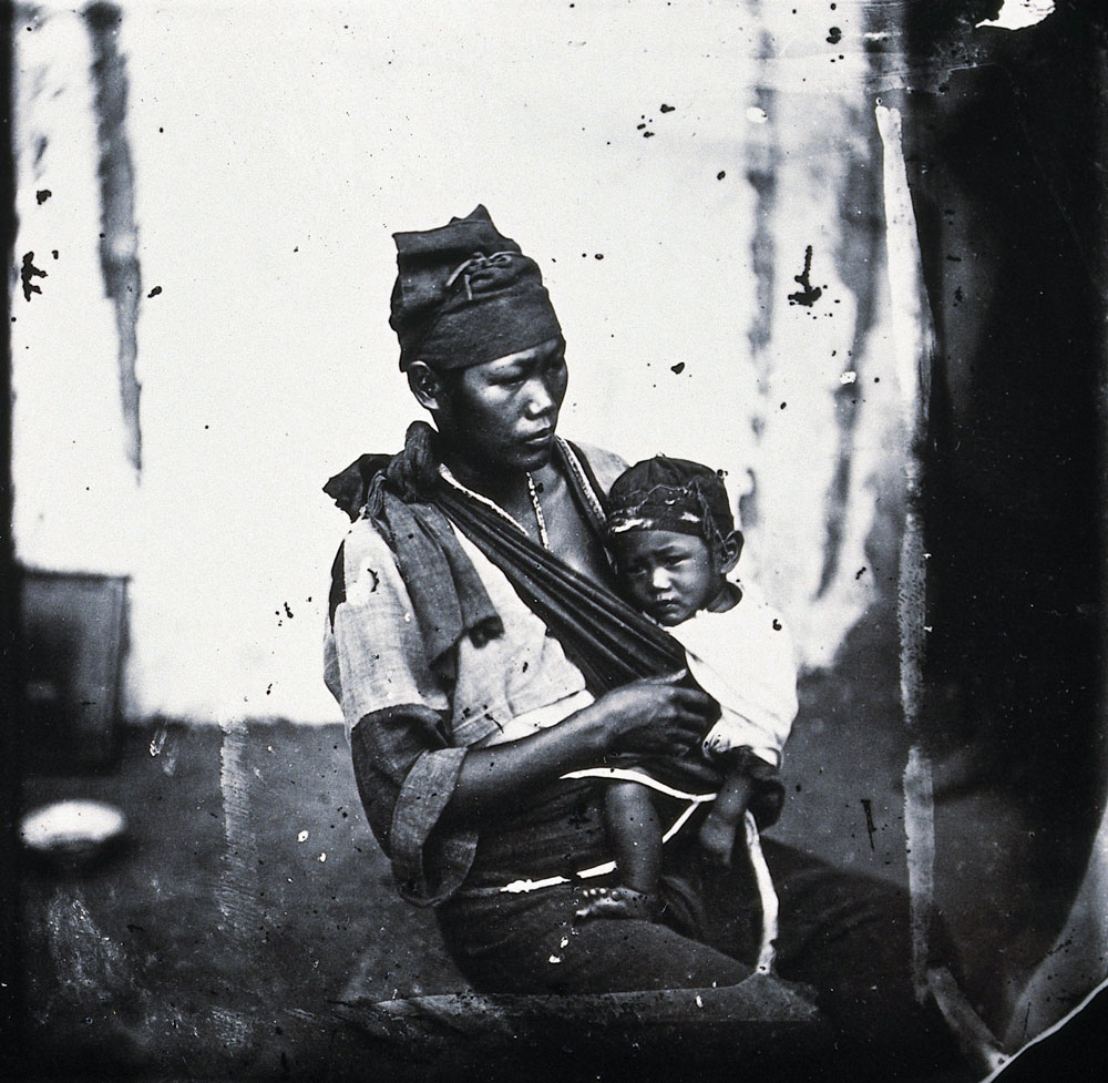 A mother, wearing a hat and coarsely-woven dress, seated with her baby, also wearing a hat, on her lap in a sling. The left-hand frame is crossed through, 1871